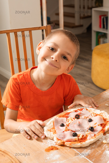 the boy delighted with cooking pizza with his own hands