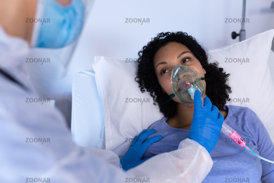 Caucasian doctor in ppe suit checking on female patient in hospital bed with oxygen ventilator