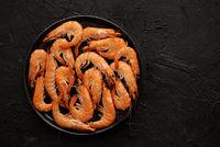 Boiled big sea prawns or shrimps placed on black ceramic plate