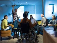 Disabled businessman in a wheelchair at work in modern open space coworking office with team using virtual reality googles drone assistance simulation