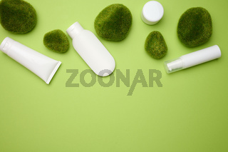 jar, bottle and empty white plastic tubes for cosmetics on a green background. Packaging for cream, gel, serum, advertising and product promotion, mock up
