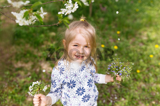 Little girl with spring flowers on green lawn in the garden