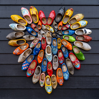 close up view of many colorful traditional clogs hanging on the wall of a house in the Netherlands