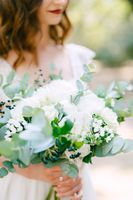 The bride is holding a wedding bouquet of roses, eucalyptus branches, delicate white flowers and dark berries in her hands, close-up