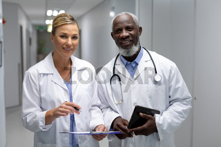Portrait of diverse male and female doctors standing in hospital corridor smiling to camera