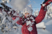 girl throwing fresh snow at beautiful sunny winter day