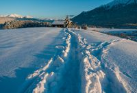 Deep snow trail path in sunlit alpine winter landscape in Wildermieming, Tirol, Austria