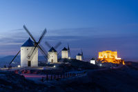 A view of the windmills and castle of Consuegra in La Mancha in central Spain at night