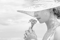 Portrait of young beautiful cheerful woman wearing straw sun hat, smelling small bouquet of yellow wild florets, against blue summer sky