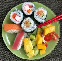 green sushi plate with green sticks and fruit