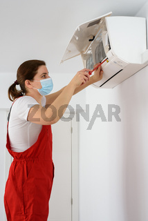 Female technician wearing face mask and repairing air conditioner
