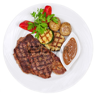 Grilled steaks, baked potatoes and vegetables on white plate on white background.