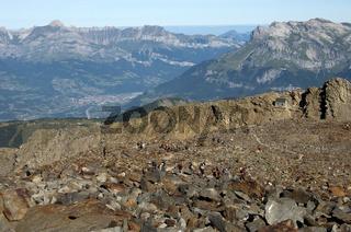 Wanderer und Alpinisten in einem Geröllfeld unterhalb der Tete Rousse Hütte auf der Normalroute zum Mont Blanc