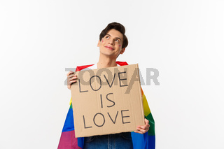Dreamy young queer person smiling and looking at upper left corner, holding love is love sign for pride parade, wearing Rainbow flag, white background