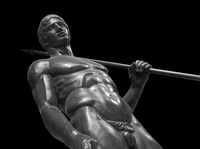 Ancient naked strong man sculpture. Young male athlete with spear statue isolated on black background