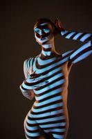 Nude woman standing in dark studio with striped illumination