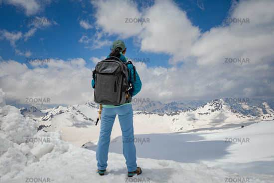Hiker woman standing up achieving the top. View at the snowy mountains.