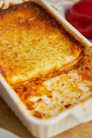 Meat lasagna with tomato sause and melted cheese in white baking dish