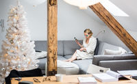 Young female entrepreneur wearing cosy warm bathrobe working remotly from home in winter Christmas time during corona virus pandemic. Work from home, selter in place, concept.
