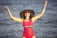 Happy woman at the sea in the sun. Woman in a swimsuit splashes water on a background of waves. Summer vacation on the beach.