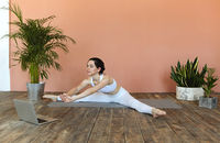 Young woman having online yoga session at home