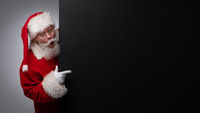 Santa Claus pointing black billboard
