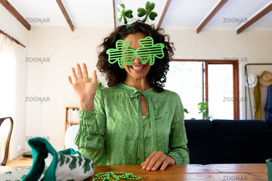 Caucasian woman dressed in green with shamrock glasses for st patrick's day waving during video call