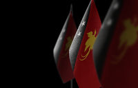 Small national flags of the Papua New Guinea on a black background