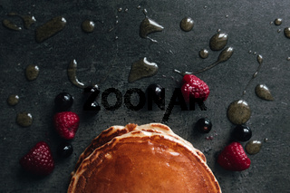 Juicy pancakes with berries, honey, spoon on a black and gray concrete table
