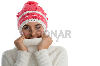 Portrait of woman wearing knit hat while covering face with turtleneck sweater
