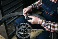Male mechanic working in bicycle repair shop, mechanic repairing bike using special tool, wearing protective gloves. Young attractive serviceman fixing customer's bicycle wheel at his own workshop