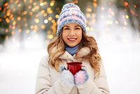 happy young woman with tea cup outdoors in winter