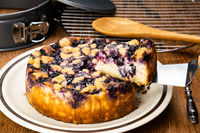 Using metal serving shovel taking a piece of homemade blueberry and crumble cheesecake.