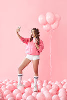 Full length portrait of trendy young woman making selfie photo on smartphone holding milk shake