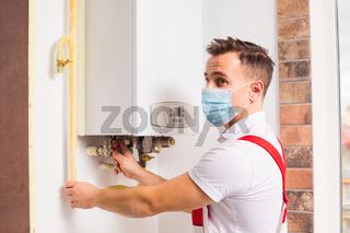 The plumber repairs a boiler in a medical mask