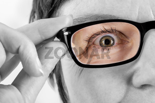 Woman holding glasses to see better