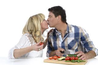 Glückliches reifes Ehepaar küsst sich beim Kochen