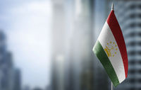 A small flag of Tajikistan on the background of a blurred background