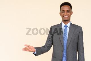 Portrait of handsome African businessman showing copy space against plain background