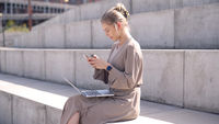 Young female using devices on street