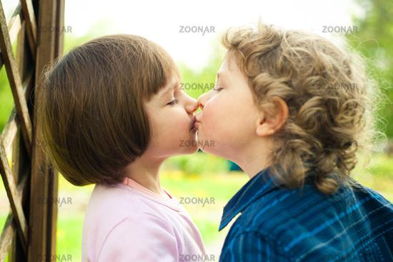 little boy kisses girl