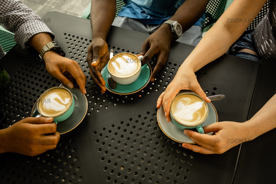 Group of people holding coffee cups, top view