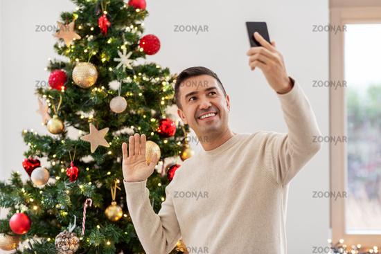man with smartphone having video call on christmas