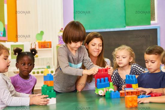 Kinder und Erzieherin beim Bauen mit Bausteinen