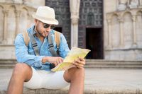 Handsome tourist man pointing at map searching the direction of destination. Travel concept. Trip, backpacker tourist.
