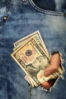 Hand holds US dollar banknotes in jeans rip hole