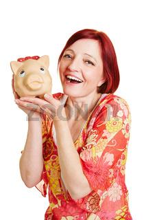 Zufriedene Frau hält Sparschwein