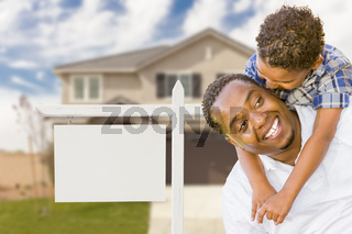 African American Father and Mixed Race Son In Front of Blank Real Estate Sign and House