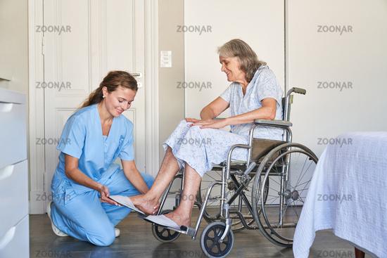 Altenpflegerin hilft Seniorin im Rollstuhl beim Schuhe anziehen