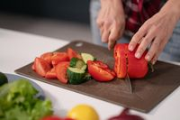 Cuts vegetables for a fresh salad young housewife cut bell pepper, cucumber, tomato on cutting board preparing for a family dinner standing in the new kitchen of a new home. Healthy lifestyle